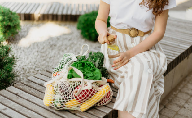 Image of conscious shopper with mesh bag of vegetables and eco-products