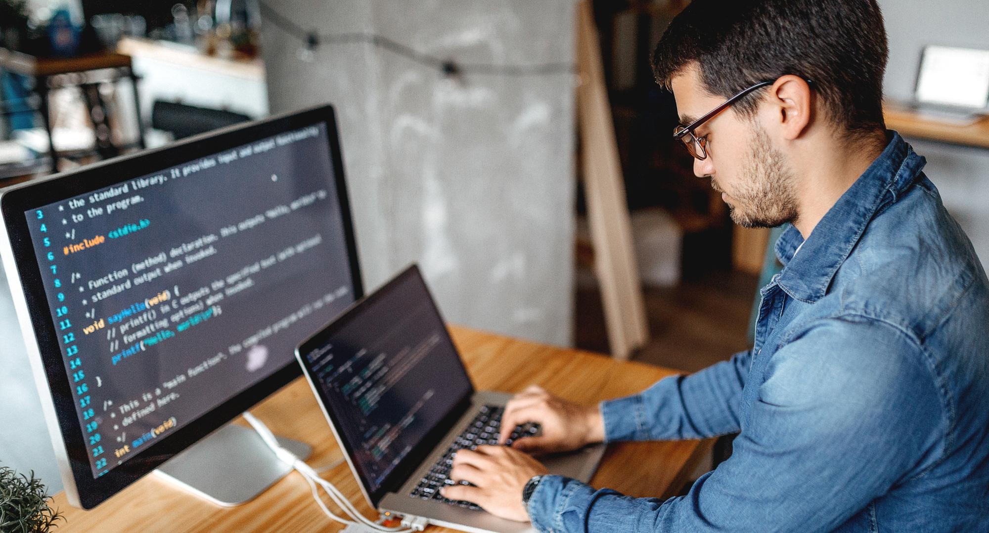 Image of man sitting at desk typing on laptop - iStock image